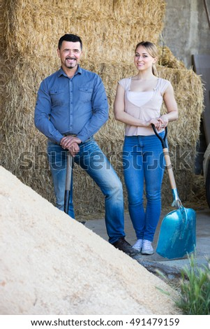 Man and young woman standing with metallic spades in hangar with sand pile