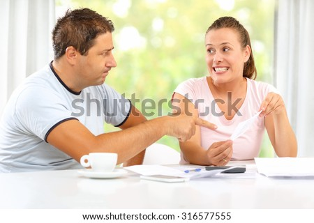 Man angry with his wife spending money and she tries to lighten up his mood. - stock photo