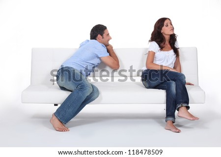 Man apolgising to woman on couch - stock photo