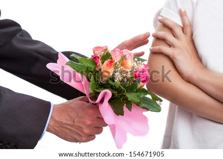 Man apologizing a women and giving her a bouquet of flowers - stock photo