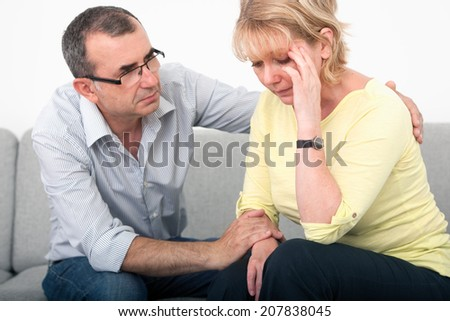 Man apologizing after an argument with his wife in the living-room - stock photo
