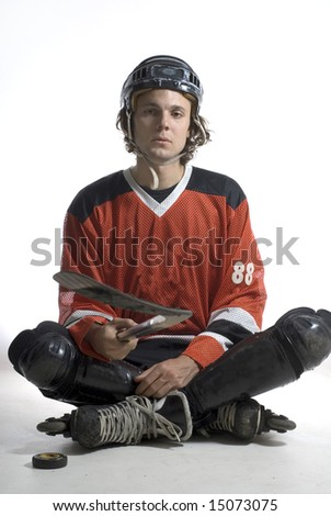 Man appears sad as he sits on the floor holding a hockey stick. Vertically framed photograph - stock photo
