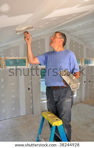 Man applying joint compound to seams between drywall panels on a ceiling - stock photo