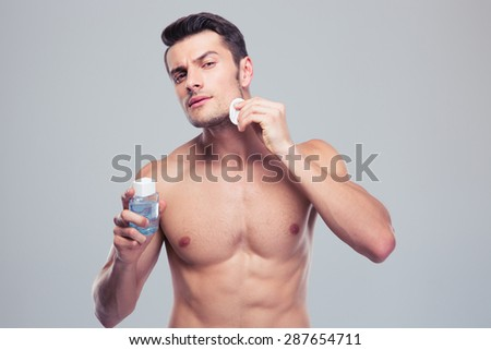 Man applying lotion after shave on face over gray background - stock photo