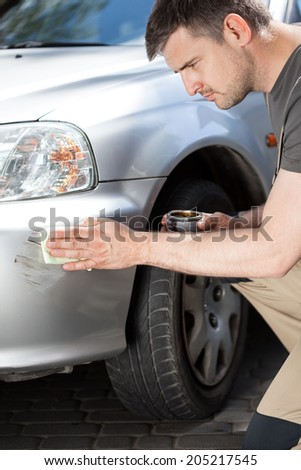 Man applying polish to removing scratches, vertical