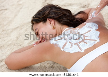 Man applying sun cream on a woman's back while in holidays - stock photo