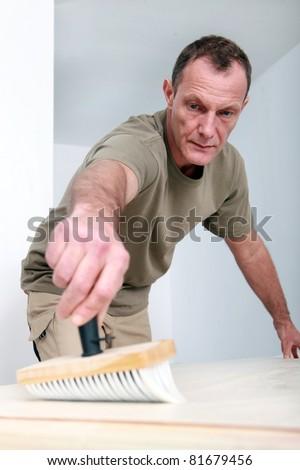 Man applying wallpaper paste - stock photo