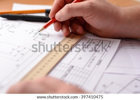 Man architect draws a plan, graph, design, geometric shapes by pencil on large sheet of paper at office desk. Soft focus