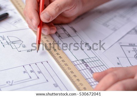 Man architect draws a plan, graph, design, geometric shapes by pencil on large sheet of paper at office desk.
