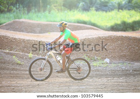 Man are riding mountain bikes uphill in a desert landscape. - stock photo