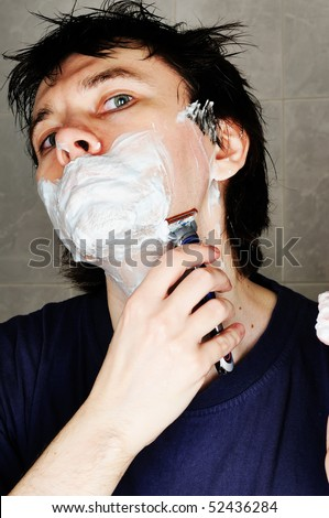 Man are shaving in the bathroom. Looking into the camera. Close-up.