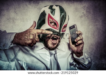 man arguing by phone, aggressive executive suit and tie, Mexican wrestler mask - stock photo