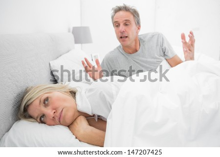 Man arguing with his partner in bed at home in bedroom