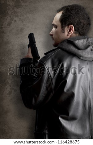 Man armed with gun on black textured background - stock photo