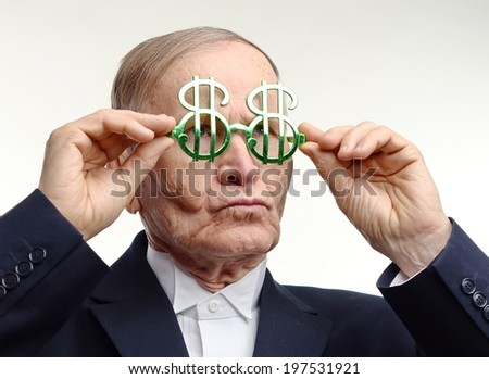 Man arranging his dollar sign glasses  - stock photo