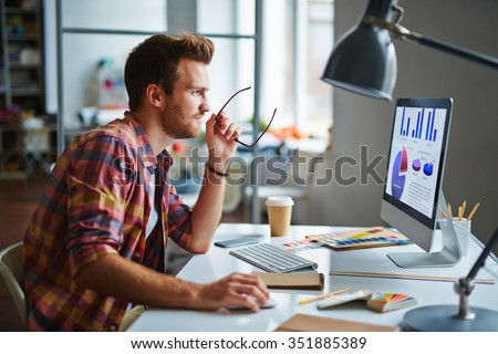 Man as a designer sitting at his table and working on computer - stock photo