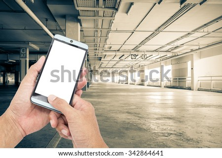 Man asia hand hold and touch screen smart phone,on Parking garag interior, industrial building,Empty underground parking background,Concept of communication anywhere, anytime. - stock photo
