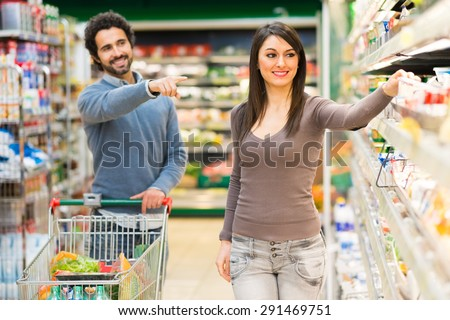 Man asking his girlfriend to buy a product in a supermarket - stock photo