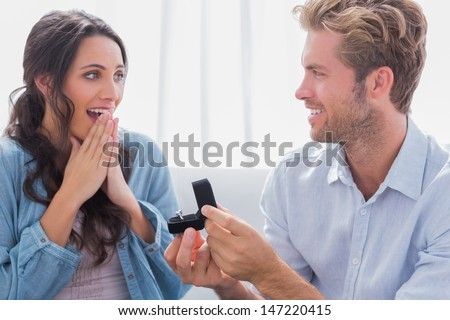 Man asking his partner to marry him by offering to her an engagement ring - stock photo
