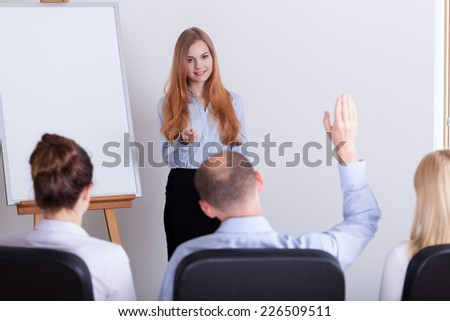 Man asking the question during the woman's lecture  - stock photo