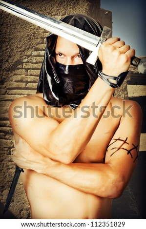 Man assassin with sexy torso in black mask and hood holding  knife and sword in hands - stock photo
