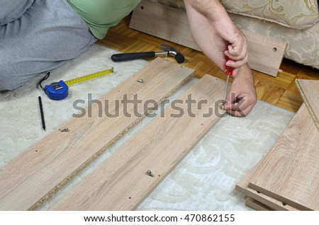 Man assembling a drawer of a new cabinet with DIY tools