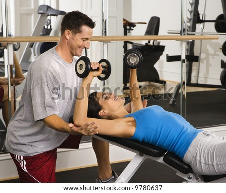 Man assisting woman at gym with hand weights smiling. - stock photo