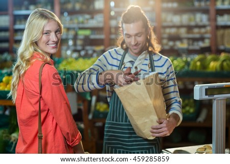 Man assisting woman in selecting vegetables in supermarket