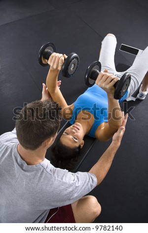Man assisting woman lifting weights at gym. - stock photo