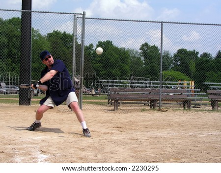 Man at a baseball diamond about to hit a softball (baseball) with ball frozen in air - stock photo