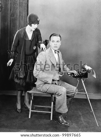 Man at a typewriter holding a gun and a  woman tapping on his shoulder - stock photo