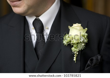 man at a wedding or funeral wearing black suit with rose buttonhole