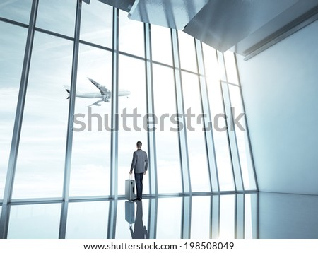 Man at airport with suitcase - stock photo
