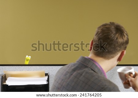 Man at cubicle desk looking at puppet - stock photo