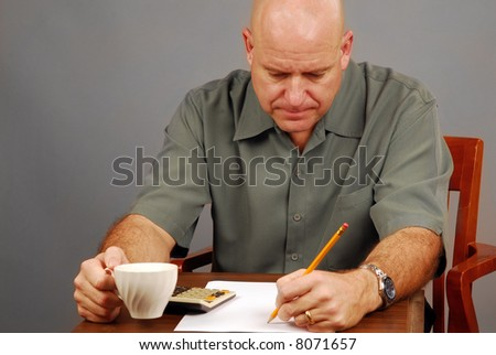 Man at Desk Drinking Coffee Working on Budget with Calculator - stock photo