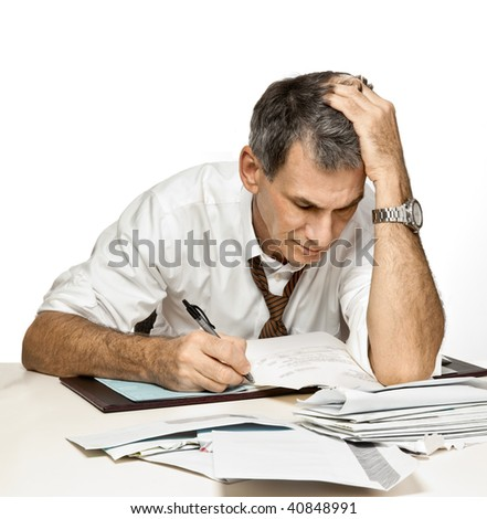 Man at desk in shirt and tie paying bills, writing checks and feeling frustrated and worried. - stock photo