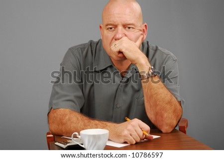 Man at desk with calculator and note paper looking serious or thoughtful - stock photo