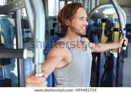 Man at fitness gym. Man doing workout on fitness machine at gym. Gym trainer athlete working out chest muscles doing strength training exercises on gym benchpress equipment. Fitness healthy lifestyle.
