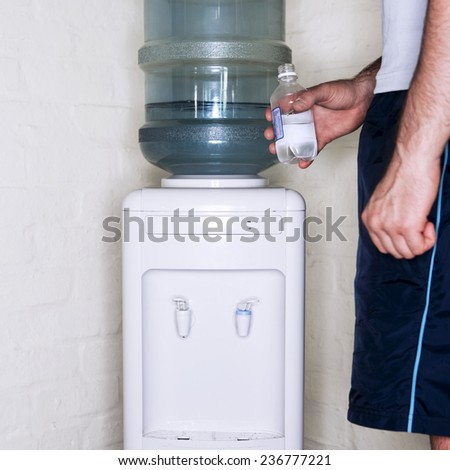 Man at Gym Filling Up Water Bottle - stock photo