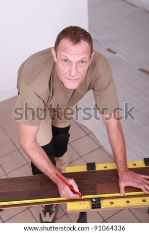 Man at home cutting wooden flooring to size - stock photo