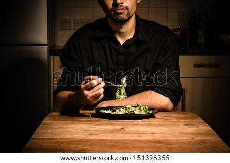 Man at home having dinner - stock photo