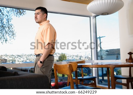 Man at home standing near window - stock photo