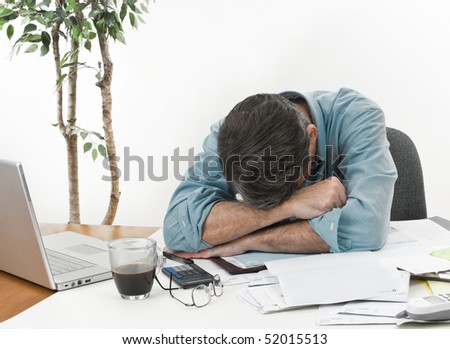 Man at office desk in with his head on his arms, worrying about paying the bills. - stock photo