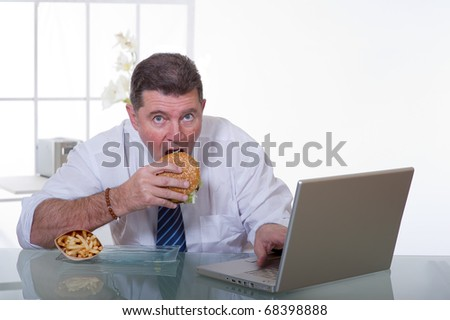 man at office  eat unhealthy fast food - stock photo
