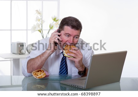 man at office with phone eat unhealthy fast food - stock photo