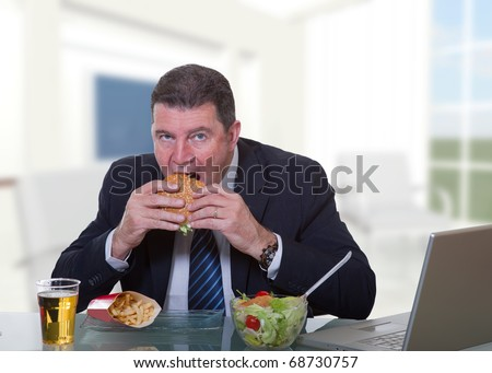 man at office working and eat unhealthy fast food - stock photo