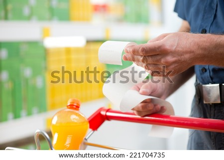 Man at supermarket examining a long grocery receipt with shopping cart on foreground. - stock photo