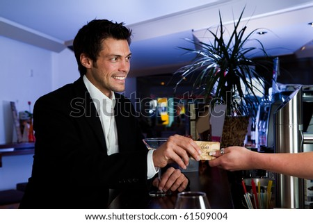 Man at the bar paying with gold credit card - stock photo