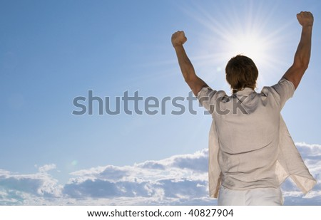 Man at the beach rising hands - stock photo