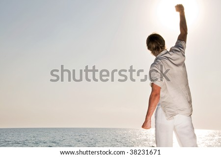 Man at the beach rising the hand - stock photo